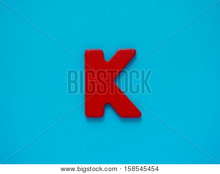 Capital letter K. Red letter K from wood on blue background.