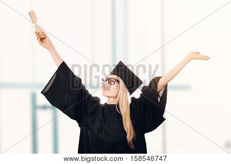 happy university graduate wearing cap and gown and holding diploma in hand