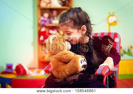 Cute Little Girl In Wheelchair Telling Her Secret To Plush Bear In Kindergarten For Kids With Specia