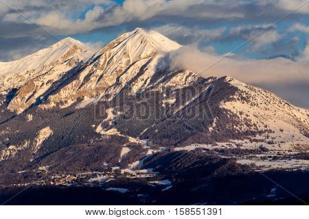Sunset on the Petite and Grande Autane mountain peaks with view on Saint Leger Les Melezes. Champsaur, Hautes Alpes, Southern French Alps, France