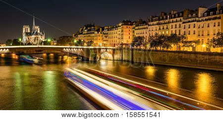 Notre Dame de Paris cathedral illuminated with Seine River and the Tournelle Bridge. Ile Saint Louis, Quai d'Orleans, 4th Arrondissement, Paris, France