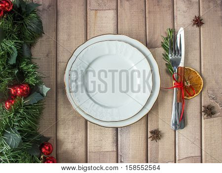 Christmas table layout, red tape with a cinnamon stick, rosmarin and a slice of dry orange on the light wooden background with christmas decorations