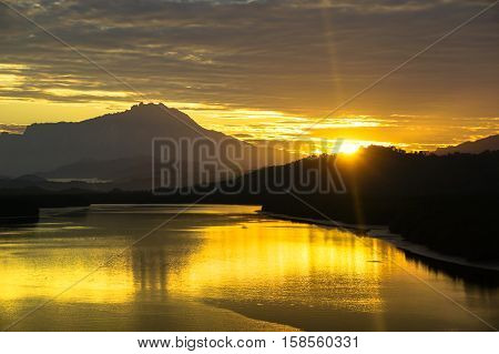 Majestic mountain Kinabalu with beautiful sunrise and amazing sky clouds at Mengkabong river,Tuaran,Sabah,Borneo.Nature view of Borneo tropical jungle.