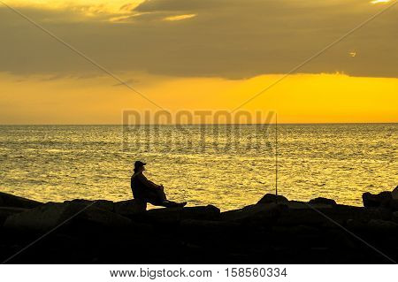 Fisherman silhouette with fishing rode on the beach during colorful sunset