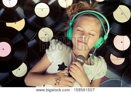 Beautiful girl lying next to vinyl records holding a microphone and listening music on headphones.Top view.