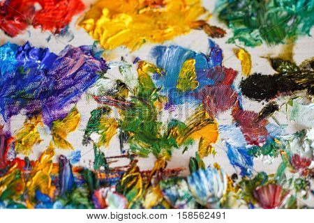 Bright art palette with colors after oil painting of artist, closeup, macro