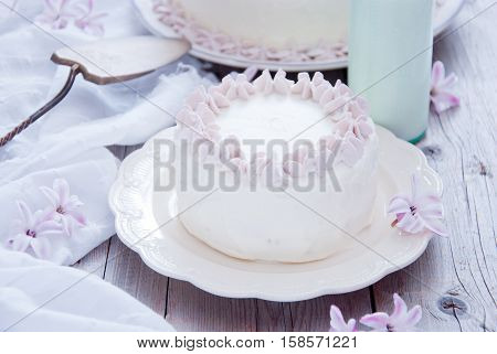 Homemade white cake with pink flowers and a bottle of milk