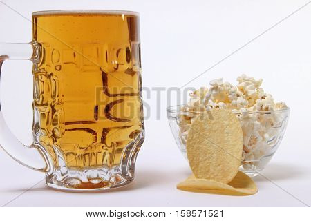 pint of cold light beer and salty popcorn on white background