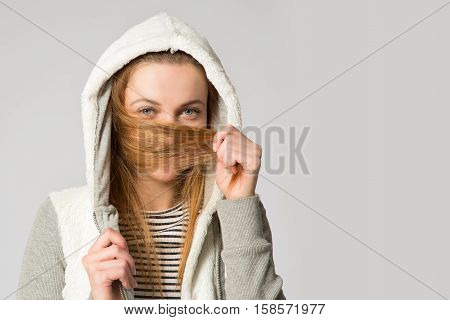 Portrait of a young woman in a hoody with long messed-up hair in her hands covering her face