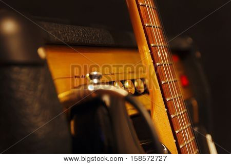 Combo amplifier for guitar with classic electric guitar on the black background. Shallow depth of field low key close up.
