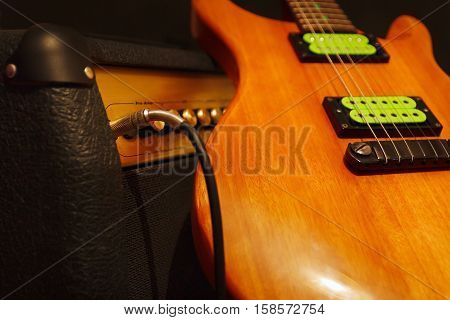 Mahogany electric guitar with combo amplifier on the black background. Shallow depth of field low key close up.