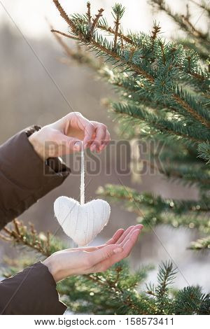 Close up of woman's hands decorating Christmas tree with white knitted heart outdoors. Presents and decor elements. Holidays and winter concept.