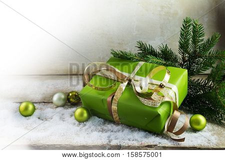 christmas and new year gift in green paper golden ribbons and baubles on a rustic wooden board with snow bright vintage background with copy space