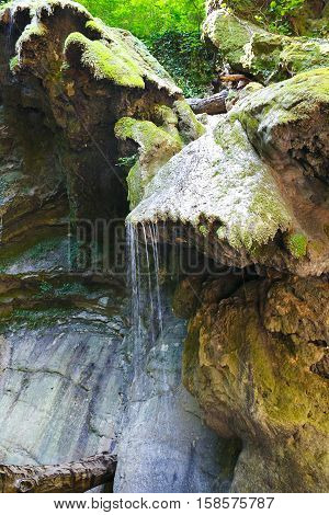 Glorious rocks with a old moss and flowing streams of water