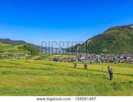 Stans, Switzerland - 7 May, 2016: view on the town of Stans from the lower part of Mt. Stanserhorn, people on a meadow in the foreground. Town of Stans is the capital of the Swiss Canton of Nidwalden.