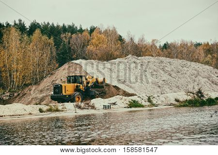 Earth-mover and a large pile of bank sand, toned image