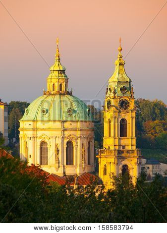 Illuminated dome and tower of St. Nicholas Church in Lesser Town of Prague - capital city of Czech republic, Europe. Evening shot at sunset time. UNESCO World Heritage Site