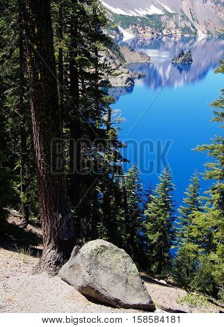 Phantom Ship in Crater Lake seen through the trees on a sunny summer afternoon.