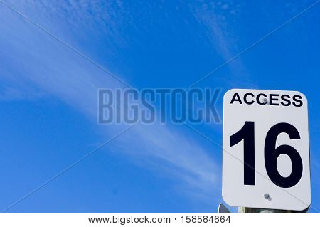 Access 16 Sign with Blue Sky and White Clouds