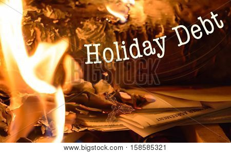 Getting our of debt holiday christmas debt image with copy space conceptual spending habits and buring credit card holder agreement in holiday fireplace with flames burning a pile of bills and statements of account with words cardholder agreement wri
