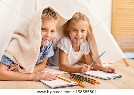 Spending time together. Smiling small brother and sister lying on floor under blanket and looking at camera