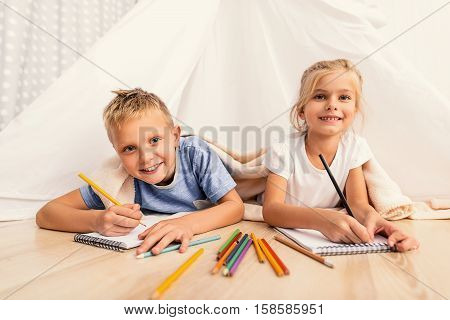 Little smiles to make your day. Happy children drawing in their playroom while lying on floor under blanket and looking at camera