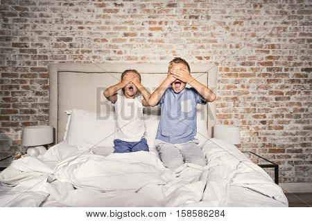 Special times together. Little screaming boy and girl sitting on bed and covering their eyes with hands