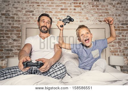 Time with dad is always great. Excited father and his little happy son playing video games. Happy little boy winning