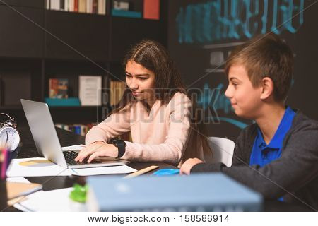 Attentive girl is sitting in dayroom with smartwatch on her hand. She is typing at laptop