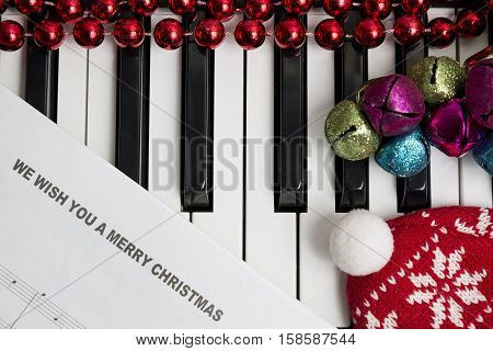 Christmas music concept. Printed music on the pianto with jingle bells red christmas balls and hat.