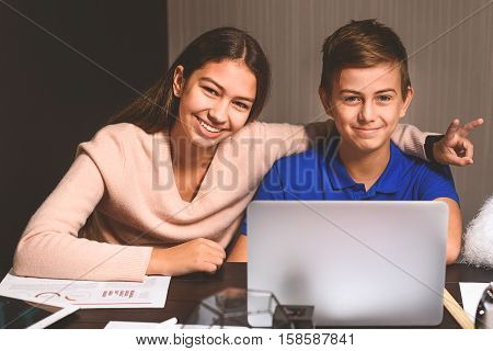 Teenagers are sitting in dayroom. Attentive boy is using computer, merry girl showing peace sign