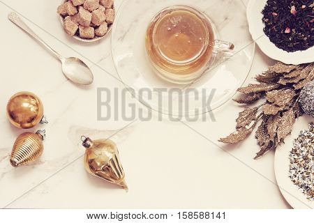 Over head flat lay view of golden herbal tea, loose tea leaves, raw sugar cubes, vintage spoon, vintage ornaments and glittered leaves. Open space for copy.