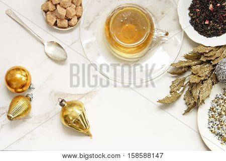 Over head flat lay view of golden herbal tea, loose tea leaves, raw sugar cubes, vintage spoon, vintage ornaments, glittered leaves. Open space for copy.