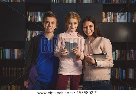Happy teenagers are standing together. They holding their gadgets