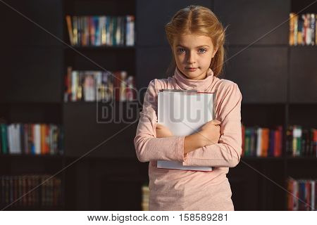 Pensive pupil is staying afore bookcase and keeping volume