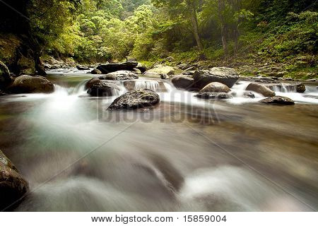 Cascade falls over old plum river with rocks