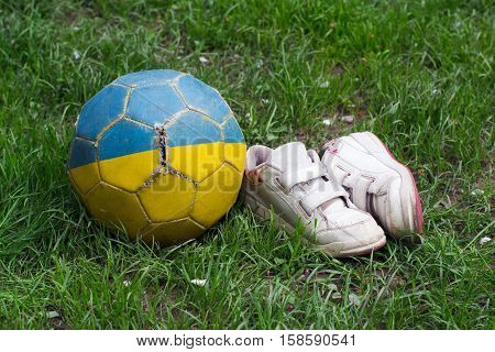 children's old shoes with worn soles and old shabby myach football on grass