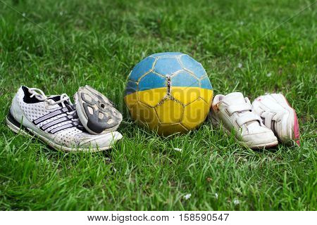 children and adults old shoes with worn soles and old shabby myach football on grass