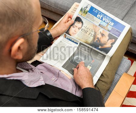 PARIS FRANCE - NOV 12 2016: Man reading Le Figaro et Vous lifestyle French newspaper