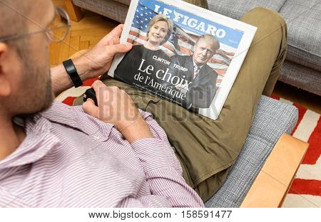 PARIS FRANCE - NOV 12 2016: Man reading Le Figaro French newspapper with Hillary Clinton and Donald Trump after Trump has wom the elections