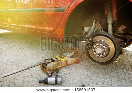Changing wheel on a red car with pressure screwdriver at the home garage