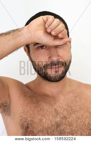 A young unshaven man looking at the camera with one hand covering one of his eyes