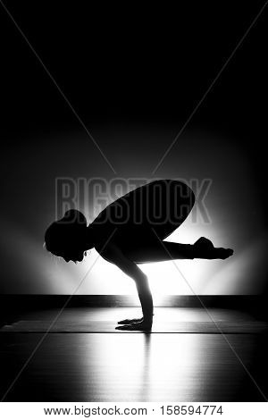 Woman doing yoga crow pose silhouette black and white in studio