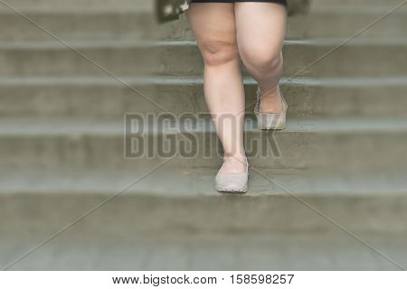 woman legs walk down stone staircase brown casual shoes and black casual dress in daytime / woman leg walk stairs
