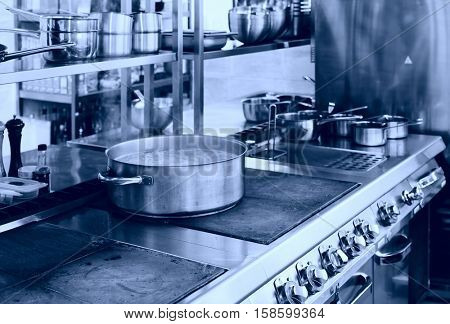 Professional kitchen interior, crock on stove, blue tone