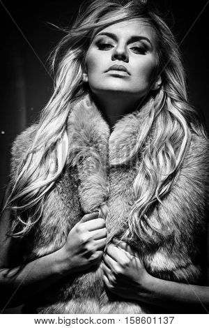 Fashion portrait of young blond woman in fur coat posing on dark background