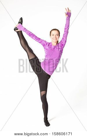 Beautiful young fit gymnast athlete woman in sportswear working out doing balance rhythmic gymnastics exercise standing splits yoga pose with one leg raised up full length studio shot