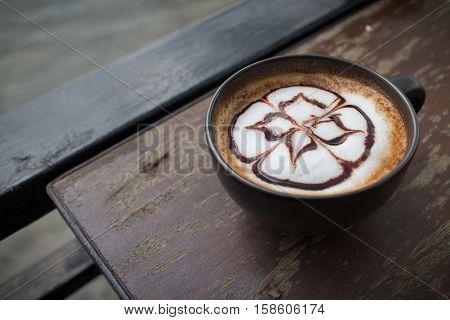 hot coffee with foam milk art. Black cup of coffee. Hot coffee in afternoon break. Coffee cup. coffee mocha on the wood desk. Coffee break.(selective focus vintage effect)