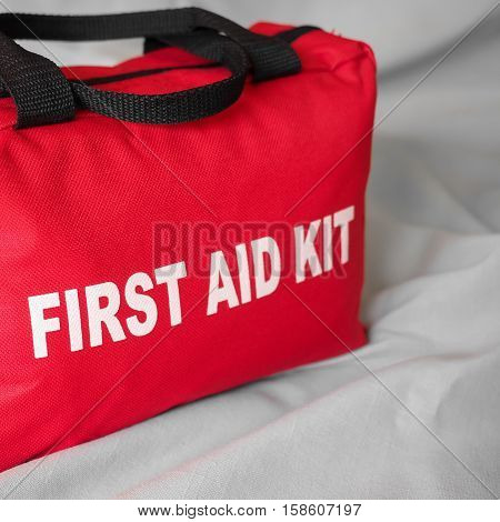 A red first aid kit bag in close up and square format on a neutral background.