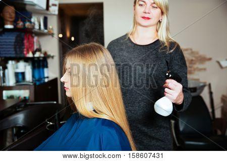 Woman hairdresser uses spray for hair